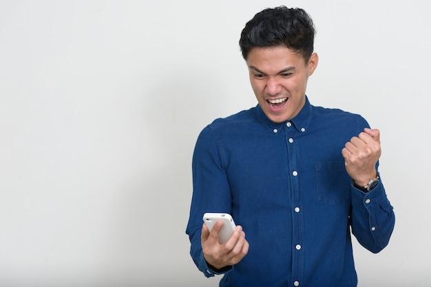 Portrait d'heureux homme d'affaires asiatique à l'aide de téléphone et obtenir de bonnes nouvelles