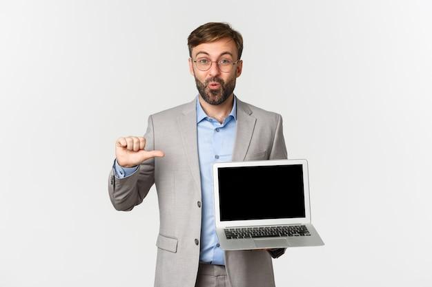 Portrait d'heureux homme d'affaires barbu à lunettes et costume gris, pointant sur ordinateur portable