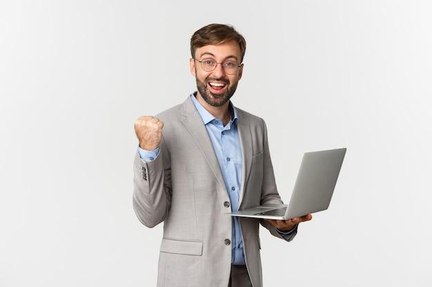 Portrait d'heureux homme d'affaires en costume et lunettes, tenant un ordinateur portable et souriant satisfait