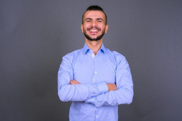 Portrait d'heureux homme d'affaires turc barbu souriant avec les bras croisés