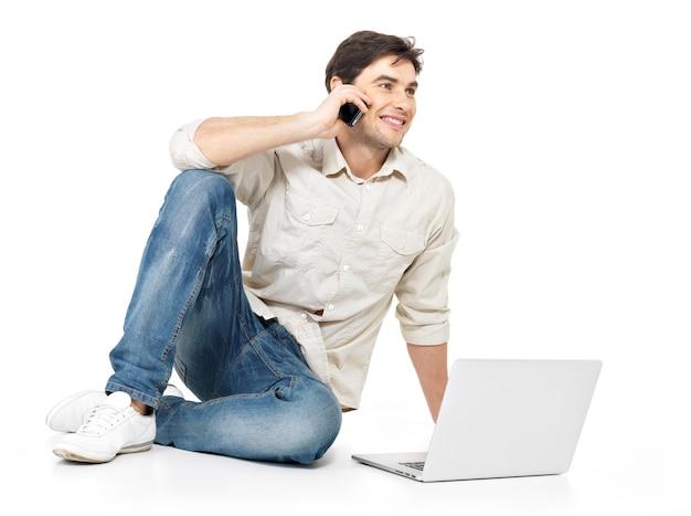 Portrait d'heureux homme appelant par mobile avec ordinateur portable dans les occasionnels isolés sur blanc.