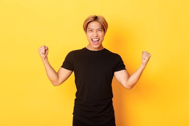 Portrait d'heureux homme asiatique attrayant se réjouissant