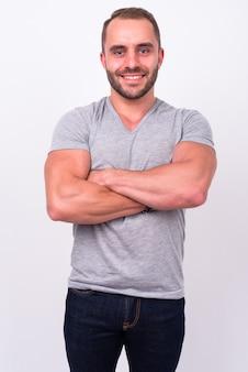 Portrait d'heureux homme barbu musclé souriant, les bras croisés