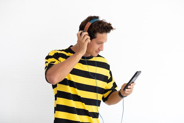Portrait heureux homme créatif hispanique écoutant de la musique en ligne sur téléphone mobile debout isolé sur fond blanc