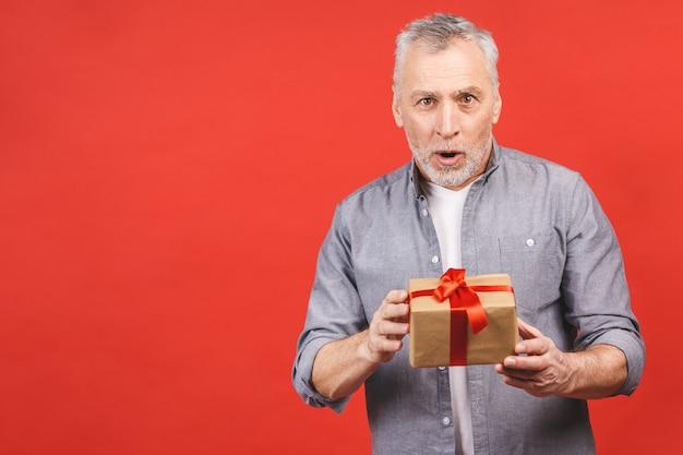 Portrait, heureux homme senior super excité, ouvert, boîtes-cadeaux déballées, isolé sur fond rouge, profitant de son présent.