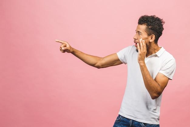 Portrait d'heureux jeune beau mâle étudiant bronzé avec une coiffure afro en souriant décontracté, pointant de côté avec le doigt, avec une expression de visage excité.