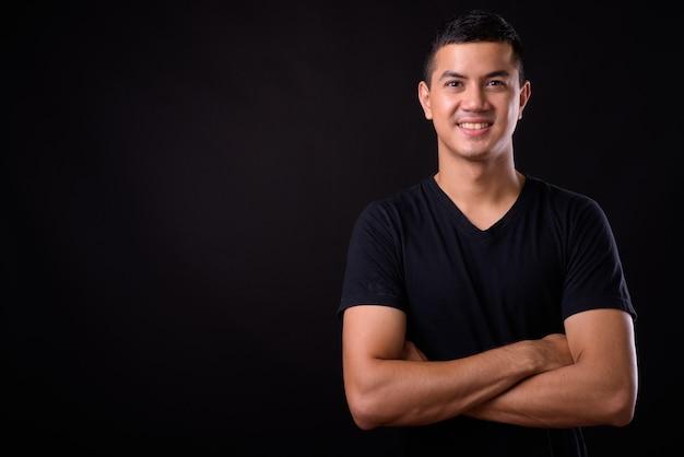 Portrait d'heureux jeune bel homme asiatique souriant avec les bras croisés