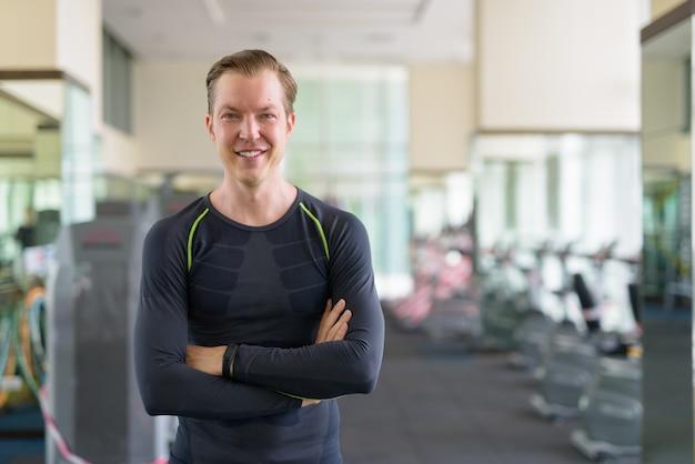 Portrait d'heureux jeune bel homme souriant avec les bras croisés à la salle de sport pendant covid-19