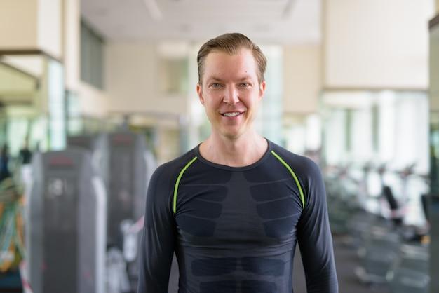 Portrait d'heureux jeune bel homme souriant à la salle de sport pendant le covid-19