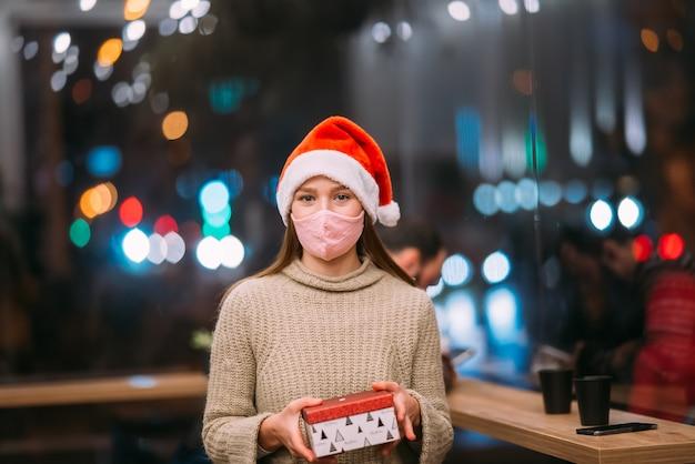 Portrait heureux jeune belle femme tenir boîte-cadeau et sourire au café