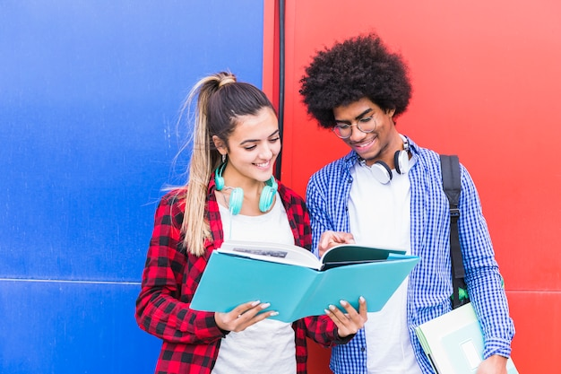 Portrait, de, heureux, jeune couple, étudier, ensemble, debout, contre, rouge, et, mur bleu