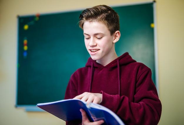 Portrait d'heureux jeune étudiant en salle de classe