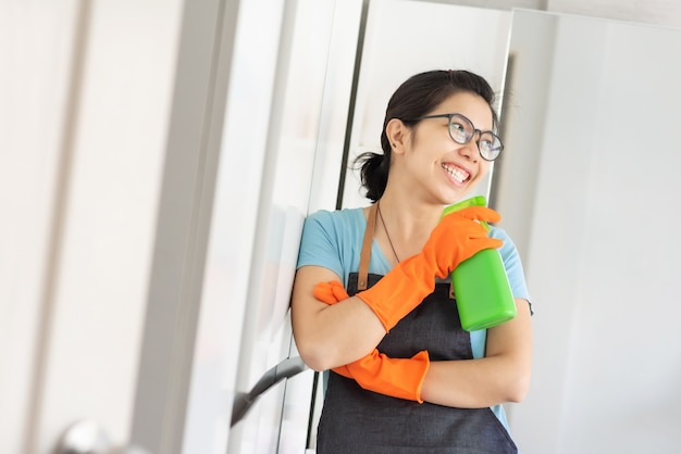 Portrait heureux jeune femme porte des lunettes tenant un vaporisateur nettoyant vert comme au micro chanter dans la salle blanche.
