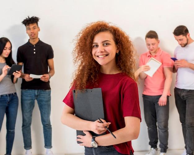 Portrait, de, heureux, jeune femme, regarder appareil-photo, tenant presse-papiers, crayon, devant, ses, amis