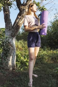 Portrait heureux jeune fille aux cheveux longs pour faire des exercices de yoga du matin sur le paysage naturel de l'herbe verte