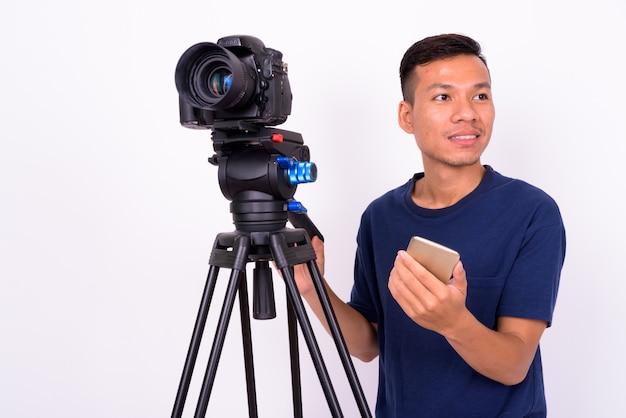 Portrait de l'heureux jeune homme asiatique avec appareil photo à l'aide de téléphone