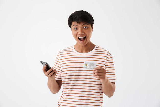 Portrait d'un heureux jeune homme asiatique célébrant