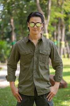 Portrait de l'heureux jeune homme asiatique en chemise à manches longues et pantalon vert debout dans le parc