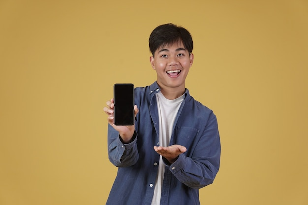 Portrait de l'heureux jeune homme asiatique habillé avec désinvolture souriant montrant écran blanc blanc smartphone isolé