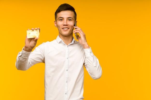 Portrait de l'heureux jeune homme asiatique tenant une carte de crédit et parler au téléphone en souriant