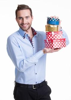 Portrait d'heureux jeune homme avec des cadeaux - isolé sur blanc.