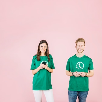 Portrait, de, a, heureux, jeune homme, et, femme, tenue, téléphone portable, devant, arrière-plan rose