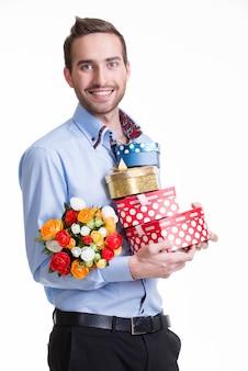 Portrait d'heureux jeune homme avec des fleurs et un cadeau - isolé sur blanc.