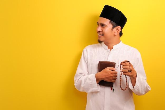 Portrait de l'heureux jeune homme musulman asiatique tenant le coran et chapelet à côté sur jaune