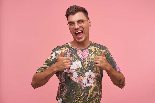 Portrait d'heureux jeune homme portant un t-shirt fleuri, le pouce vers le haut et un clin d'œil à la caméra, isolé sur fond rose, profiter de la vie