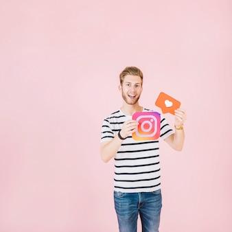 Portrait, de, a, heureux, jeune homme, tenue, instagram, et, coeur, forme, icône
