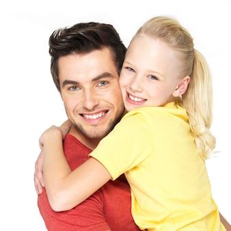 Portrait de l'heureux jeune père avec jolie fille - isolé sur mur blanc