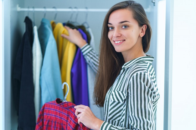 Portrait, de, heureux, jeune, smiley, brunette, femme, choisir, équipement, depuis, armoire penderie, à, élégant, vêtements, et, maison, substance