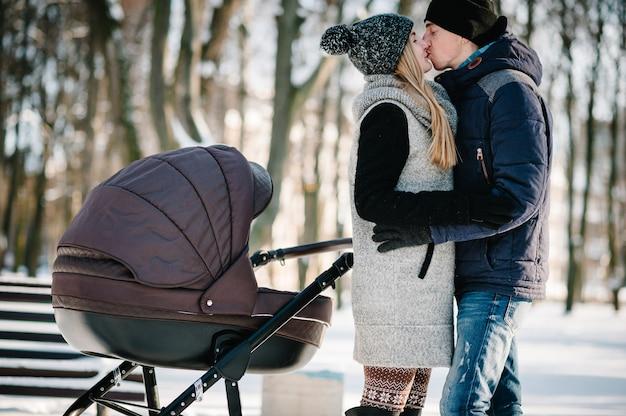 Portrait d'un heureux jeunes parents se tenir debout et s'embrasser avec un bébé poussette dans un parc d'hiver
