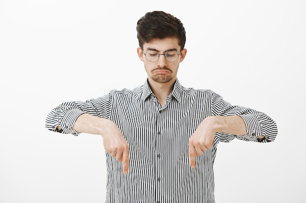 Portrait de heureux mec barbu attrayant calme en chemise rayée, pointant et regardant vers le bas avec une expression triste sombre, être déçu et contrarié par un résultat négatif sur un mur gris