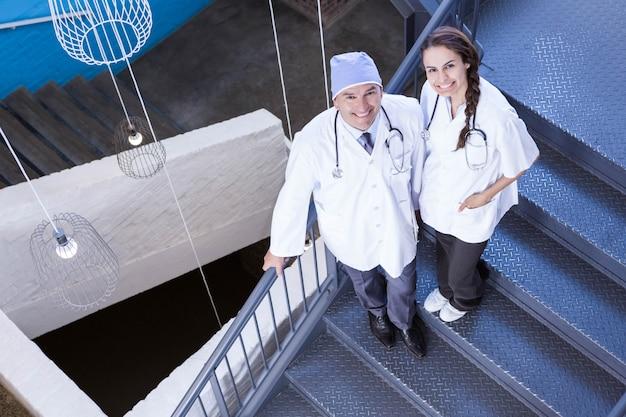 Portrait, heureux, médecins, debout, escalier, hôpital