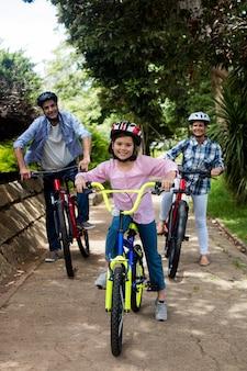 Portrait d'heureux parents et fille debout à vélo dans le parc