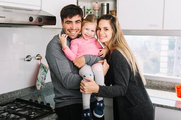 Portrait d'un heureux parents avec leur fille dans la cuisine
