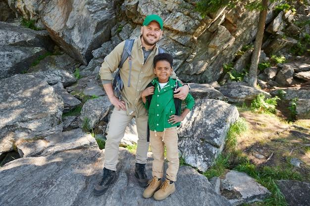 Portrait de l'heureux père embrassant son fils et souriant à la caméra alors qu'ils se tenaient sur les rochers à l'extérieur