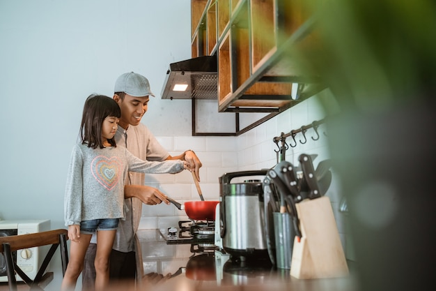 Portrait de l'heureux père et fille asiatique cuisiner ensemble dans une cuisine moderne