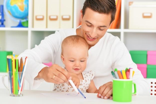 Portrait de l'heureux père et fille peignant à la maison