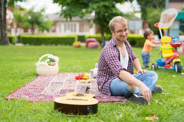 Portrait de l'heureux père et fils de bébé multiethnique de liaison ensemble à l'extérieur