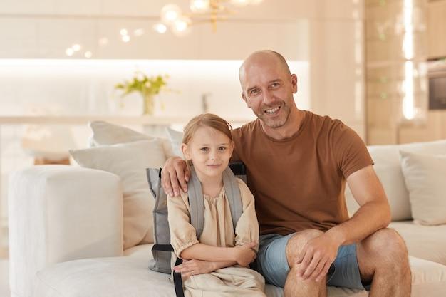Portrait de l'heureux père mature souriant tout en posant avec jolie petite fille portant un sac à dos prêt pour l'école en septembre