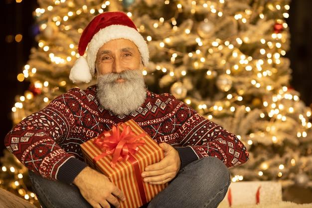 Portrait de l'heureux père noël assis dans sa chambre à la maison près de sapin de noël.