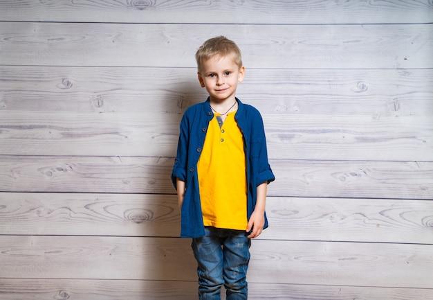 Portrait de l'heureux petit garçon blond sur blanc en bois