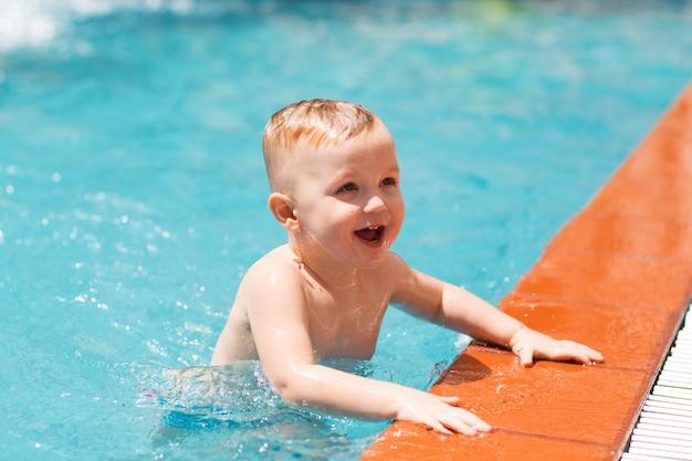 Portrait de l'heureux petit garçon nageant dans la piscine