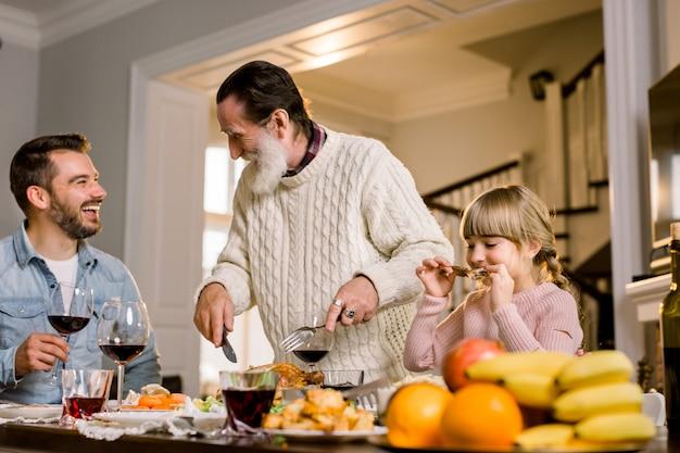 Portrait de l'heureux vieux grand-père coupe la turquie à la table de fête avec son fils et sa petite-fille