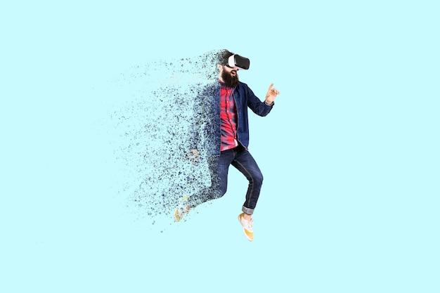Portrait d'un hipster barbu sautant dans des verres de réalité virtuelle, l'homme se dispersant et se désintégrant en particules