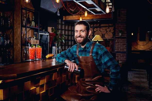 Portrait d'un hipster barman avec barbe souriant assis dans un bar