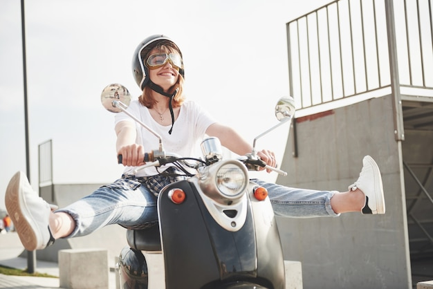 Portrait d'un hipster de belle fille assise sur un scooter rétro noir