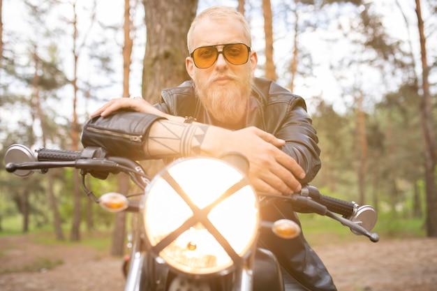Portrait hipster jeune homme avec une barbe et une moustache avec des lunettes de soleil, une moto décontractée de rue